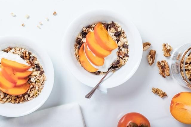 yaourts dans bols avec céréales, kakis et noix