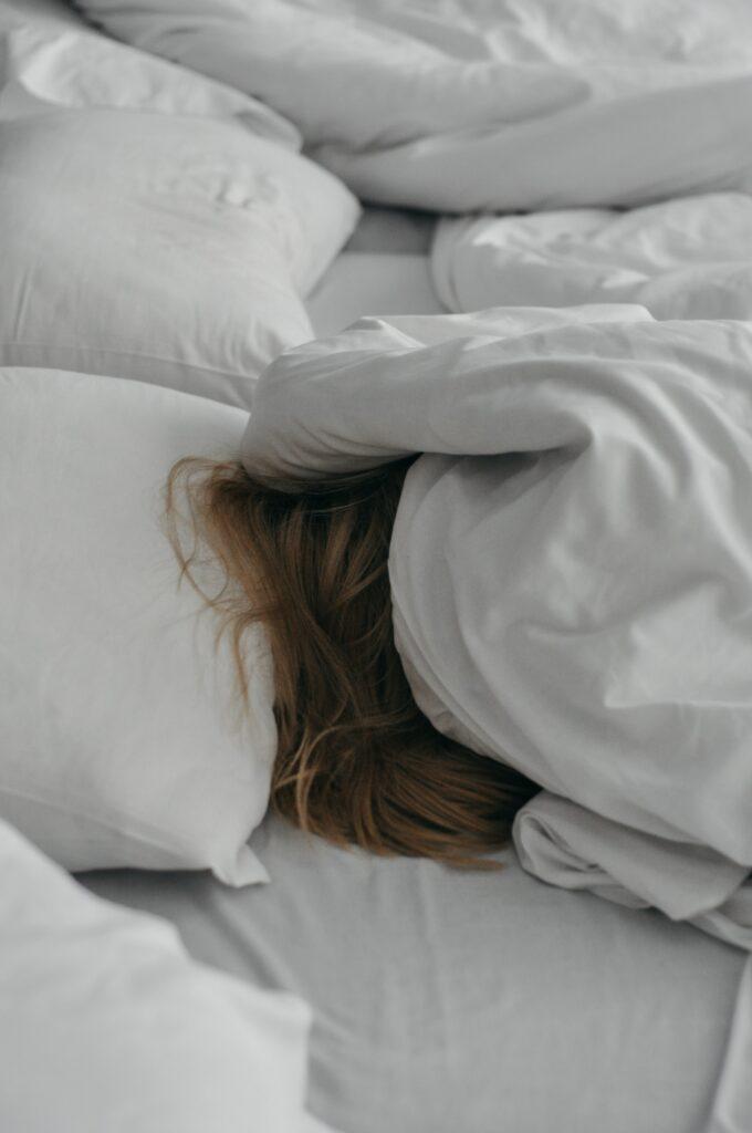 femme qui dort dans draps blancs