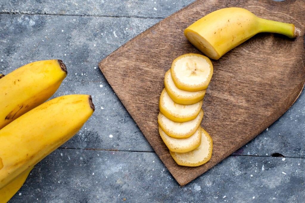 bananes et tranches de banane sur planche en bois