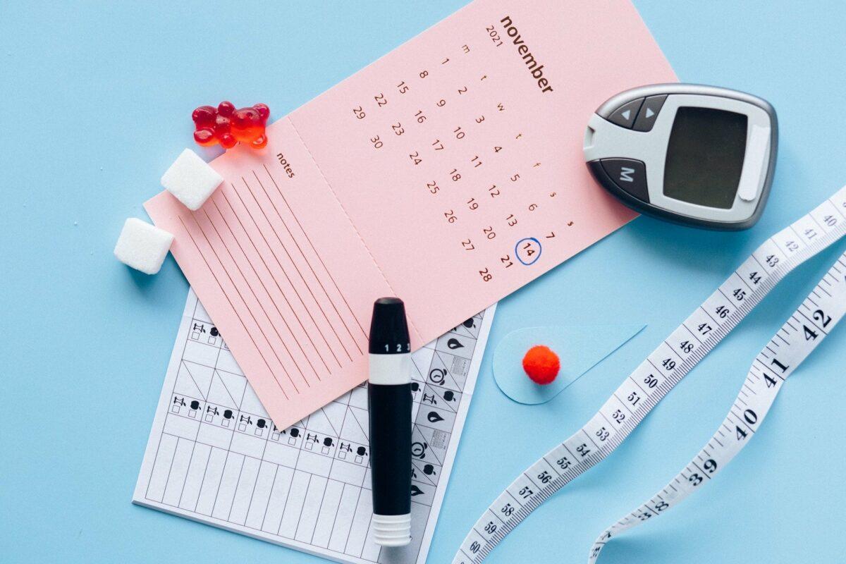 calendrier, capteur de glycémie, mètre et bonbons sur fond bleu