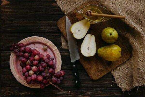 poires, raisins noirs et couteau
