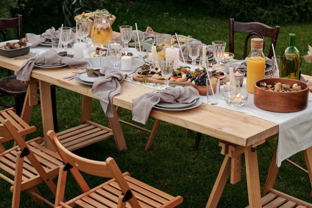 chaises en bois et table dressée avec nourriture dans l'herbe