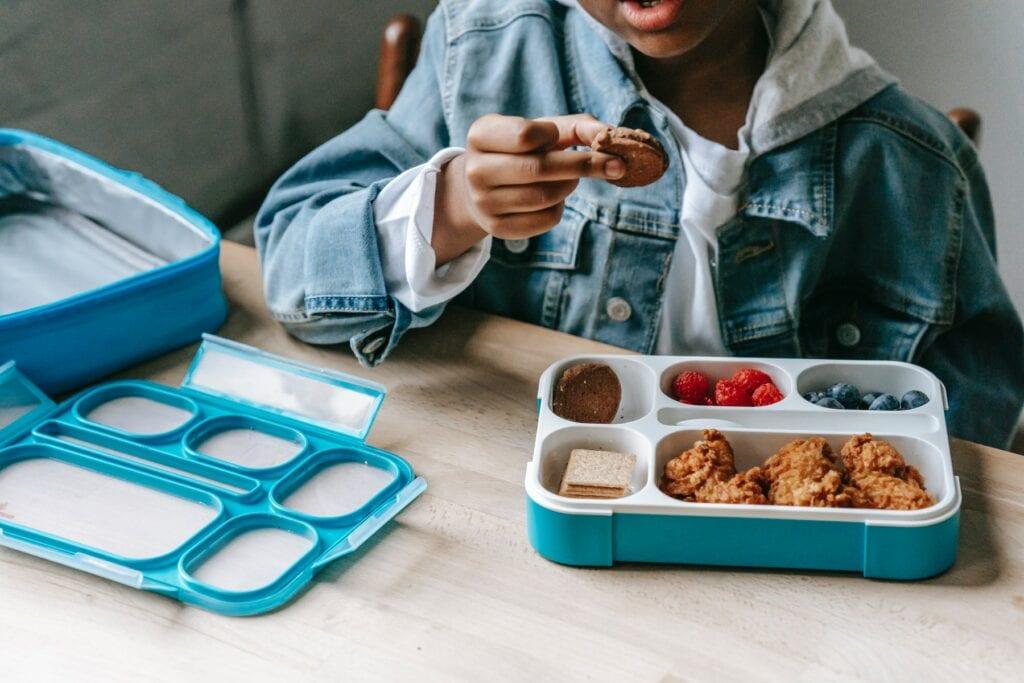 enfant qui mange dans boite à tartines bleue