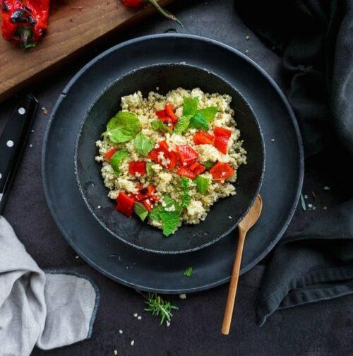 taboulé de quinoa dans assiette noire sur fond sombre