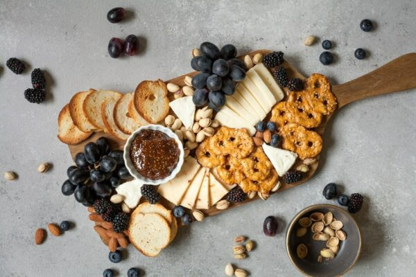 plateau de fromage avec fruits sur planche en bois et fond gris