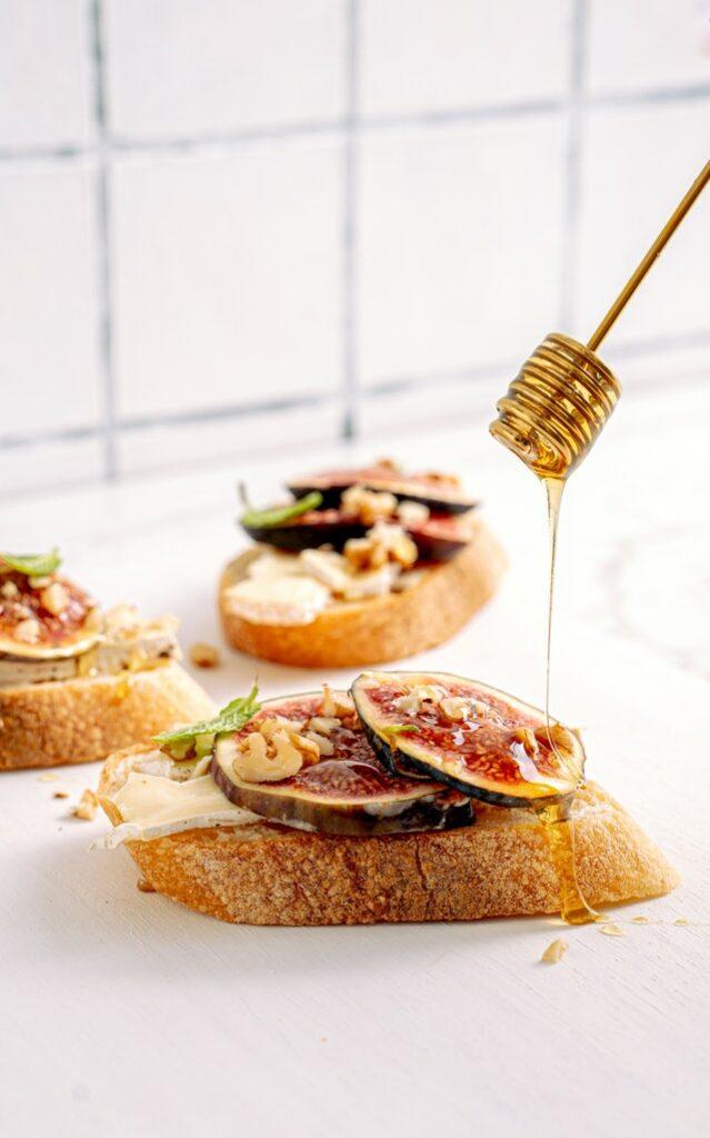 toast figue chèvre miel noix sur fond blanc