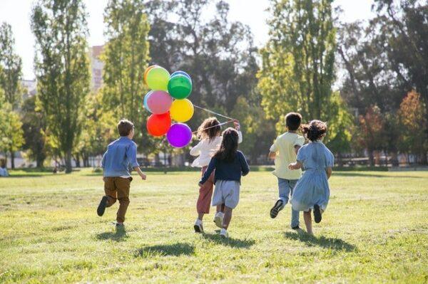 enfants qui courent dehors avec ballons colorés