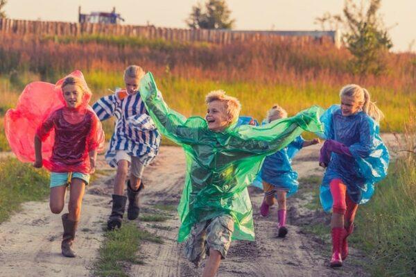 enfants qui courrent dehors avec imperméables